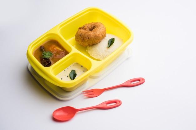 Idly o idli con medu wada sambar in lunch box di tiffin