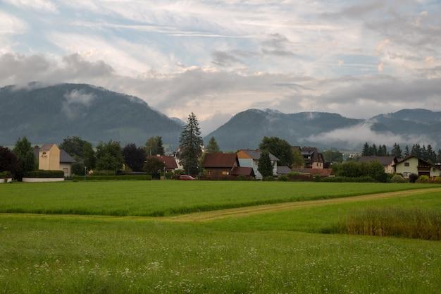 Idilliaco paesaggio alpino con prati verdi freschi, fiori che sbocciano, tipiche fattorie e montagne innevate nella luce dorata della sera al tramonto, nationalpark berchtesgadener land, baviera, germania