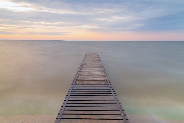 Idilliaco molo mole sul lago, ponte di legno su un lago all'alba.