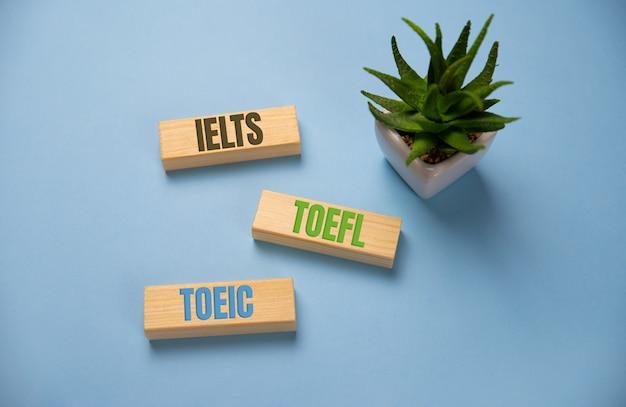 Parola di ielts, toefl, toeic su blocchi di legno sull'azzurro.
