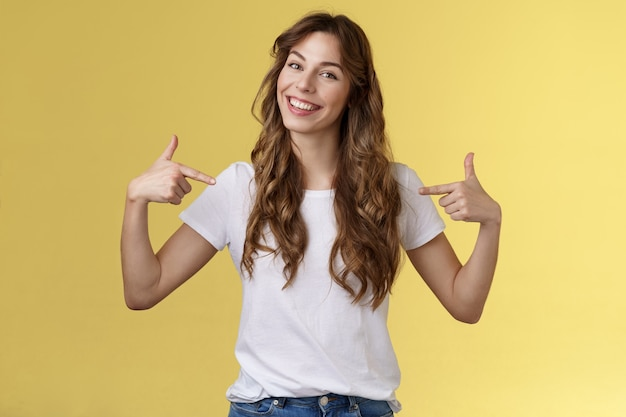 Se vuoi un professionista sono io. sassy bella e fiduciosa giovane donna in uscita si presenta vantandosi dei propri successi puntando il petto sorridendo soddisfatto sfondo giallo