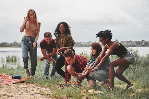 Accendere il fuoco. un gruppo di persone fa un picnic sulla spiaggia. gli amici si divertono durante il fine settimana.