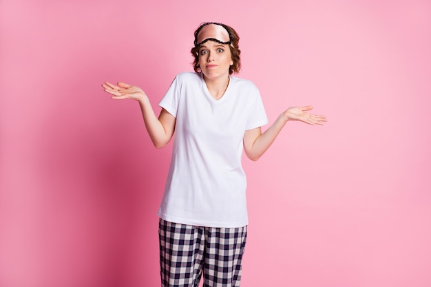 Ragazza ignorante braccia alzate alzare le spalle su sfondo rosa