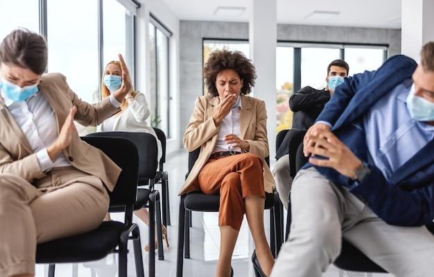 Imprenditrice malata tosse mentre era seduto con i suoi colleghi in seminario. i colleghi hanno paura del coronavirus, quindi si nascondono.