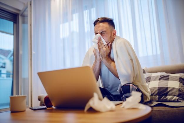 Impiegato caucasico malato in pigiama che si siede sul sofà in salone coperto di coperta e soffiando naso