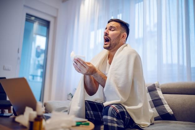 Impiegato caucasico malato in pigiama che si siede sul sofà in salone coperto di coperta e di starnuti.