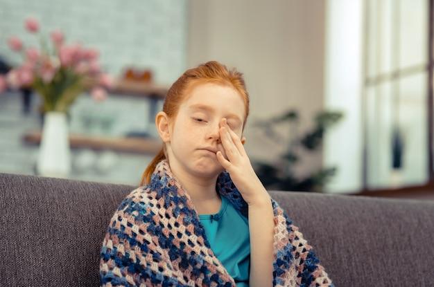 Bambino malato. ragazza pallida e triste che si strofina il viso mentre si sente male