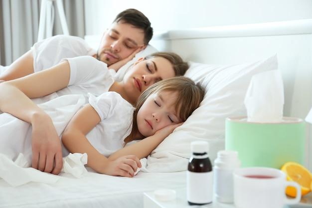 Famiglia malata che dorme nel letto di casa