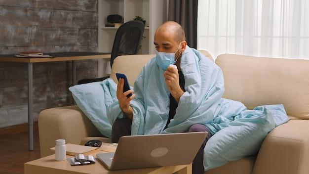 Uomo malato durante il blocco durante una videochiamata con il suo medico che parla della prescrizione.