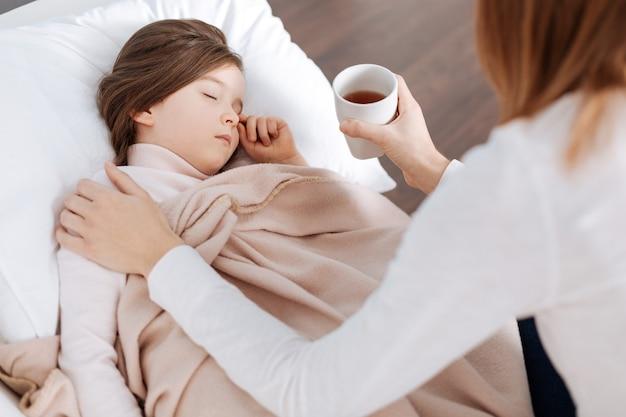 Bambina piacevole malata che dorme mentre sua madre seduta sul divano e tiene una tazza di tè