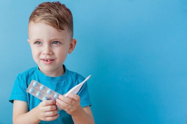 Bambino malato con un termometro, che misura l'altezza della sua febbre e guarda nell'obiettivo