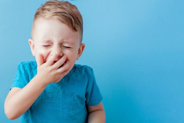 Bambino malato con un termometro, misurando l'altezza della sua febbre ed esaminando la fotocamera.