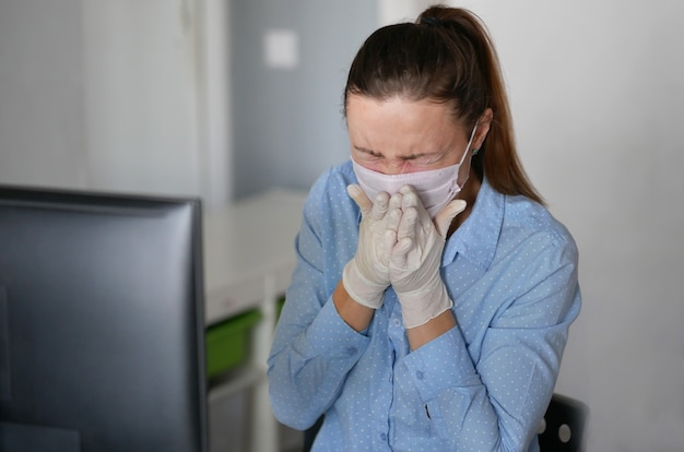 Giovane donna malata che utilizza computer portatile che indossa la maschera per il viso e tosse, lavorando da casa o in ufficio, primi piani