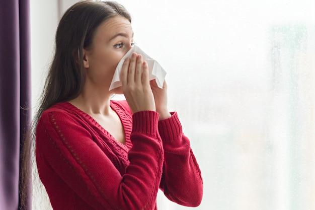 Giovane donna malata con il fazzoletto vicino alla finestra