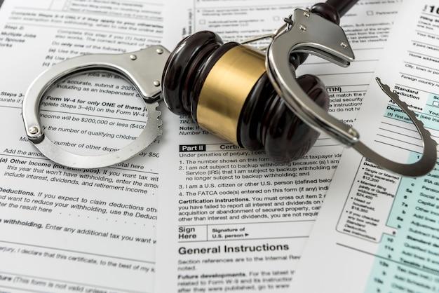 Concetto illegale modulo fiscale usa con martelletto e manette. tempo per gli affari
