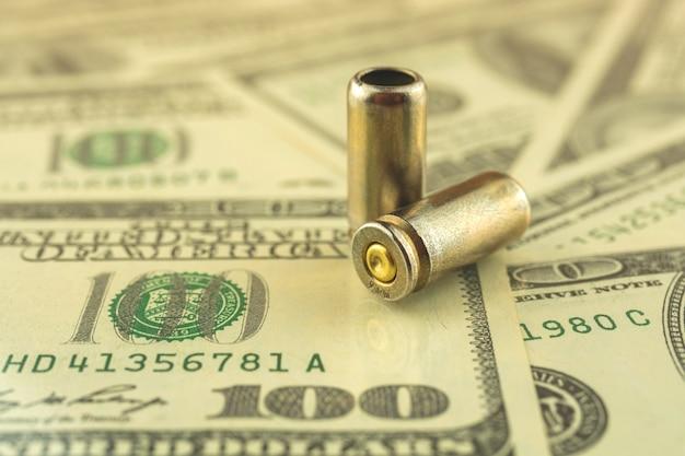 Vendita illegale, concetto di denaro criminale, dollari usa e proiettile per una pistola, cartucce di pistola da 9 mm sullo sfondo