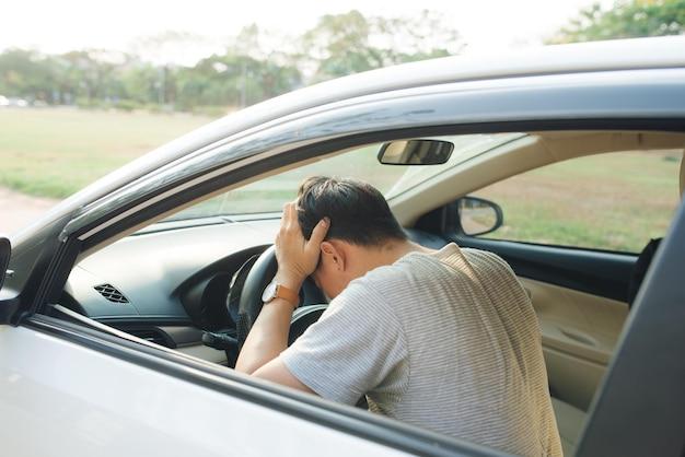 Malattia, esausto, malattia, stanco per il concetto oberato di lavoro. uomo d'affari asiatico che ha mal di testa da emicrania mentre guida l'auto.