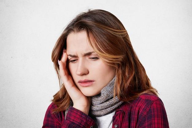Concetto di malattia e malattia. esausta stressata giovane femmina soffre di emicrania, tiene la mano sulla testa, guarda disperatamente verso il basso