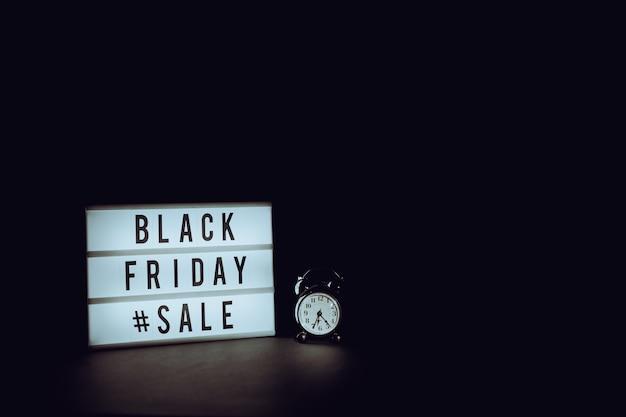 Cartello del black friday illuminato accanto a un orologio con sfondo nero e spazio di copia