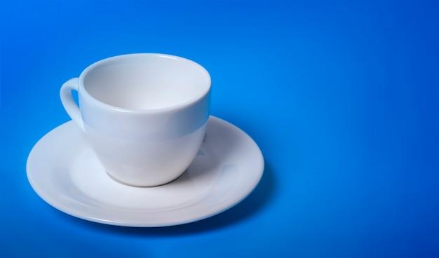 Tazza bianca vuota illuminata su sfondo blu con una copia dello spazio.
