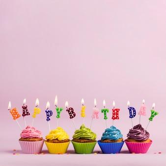Un testo di buon compleanno illuminato candele sopra i muffin colorati su sfondo rosa