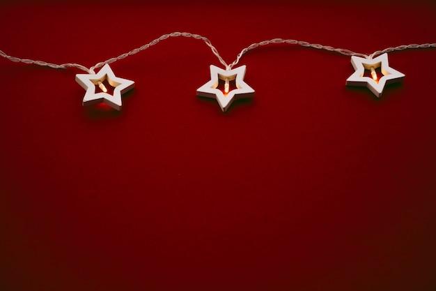 Ghirlanda a forma di stella illuminata su sfondo colorato da vicino