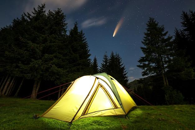 Tenda turistica illuminata su una radura verde con montagne lontane e cielo notturno stellato