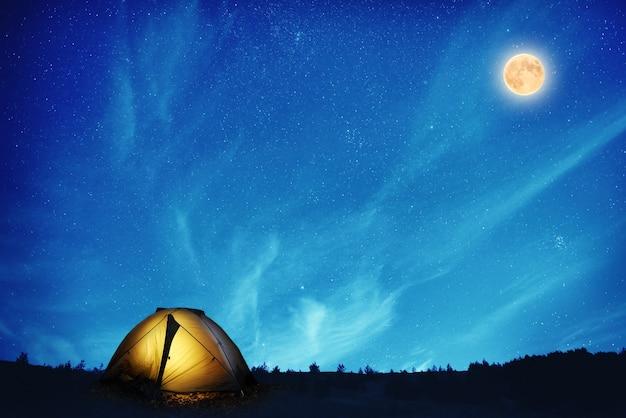 Tenda da campeggio gialla illuminata sotto molte stelle e luna piena di notte