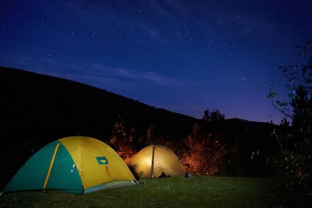 Tende da campeggio gialle illuminate sotto le stelle di notte
