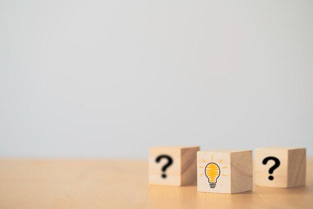 Icona della lampadina dell'illustrazione e schermo di stampa del punto interrogativo sul cubo del blocco di legno. è un'idea di pensiero creativo e un concetto di innovazione.