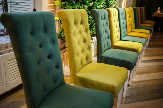 Illustrazione del salone interno moderno. fila di facile sedia in tessuto contro la parete e il pavimento blu pastello. sfondo del soggiorno. sedia verde al centro.