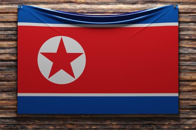 Illustrazione della bandiera nazionale del tessuto della corea del nord inchiodata su una parete di legno