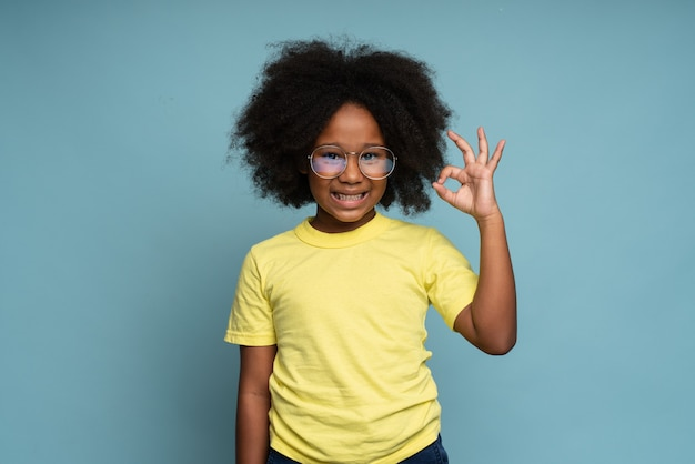 Sto bene ritratto di adorabile bambina gioiosa con i capelli ricci in maglietta gialla che mostra ok