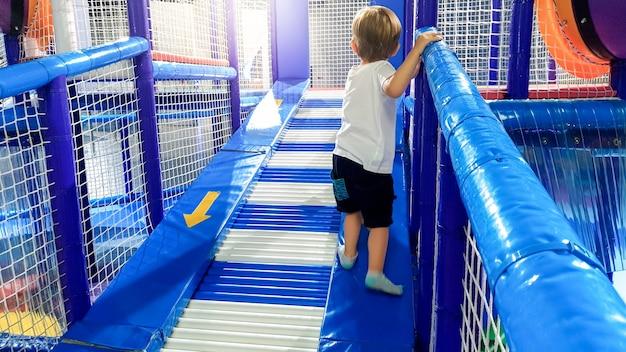 Immagine di un bambino di 3 anni che si arrampica e striscia sul campo da gioco dei bambini nel centro commerciale. ci sono molti tappetini morbidi per la sicurezza dei bambini