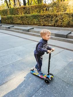 Immagine di un bambino di 3 anni che si imbarca su uno scooter nel parco autunnale