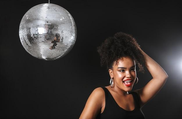 Immagine di adorabile donna africana in piedi con argento palla da discoteca