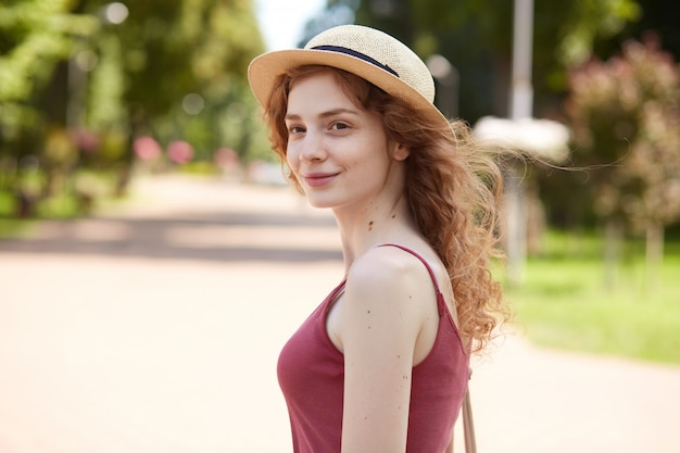 Immagine di adorabile bel giovanotto che osserva da parte, in piedi nel mezzo del parco estivo, sorridendo sinceramente, avendo un aspetto piacevole, con cappello di paglia, camicia rossa, con borsa sulla spalla. concetto di gioventù.