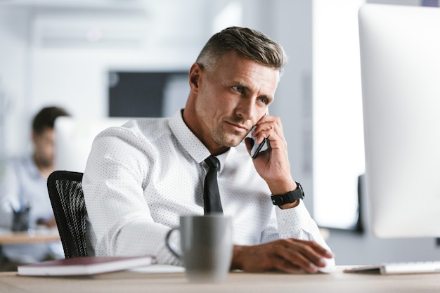 Immagine di uomo d'affari adulto 30s indossa una camicia bianca e cravatta seduto alla scrivania in ufficio dal computer e parlando sullo smartphone