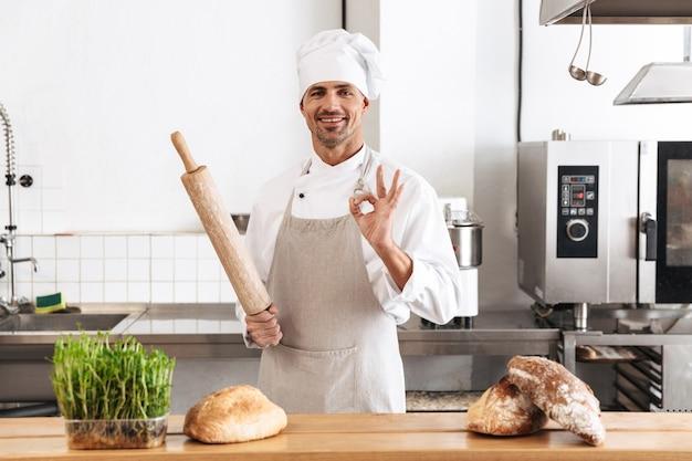 Immagine del fornaio uomo adulto in uniforme bianca sorridente, mentre si trovava al forno con pane sul tavolo