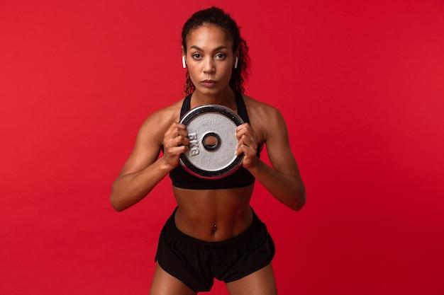 Immagine della sportiva afroamericana in abiti sportivi neri che tengono bilanciere, isolato sopra la parete rossa