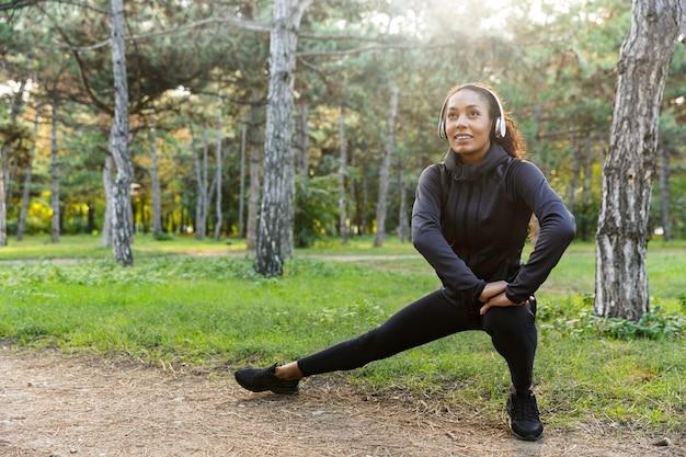 Immagine della donna afroamericana 20s che indossa la tuta nera che lavora e che allunga il corpo nel parco verde