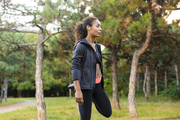 Immagine della donna afroamericana 20s che indossa la tuta nera che lavora e che allunga il suo corpo nel parco verde