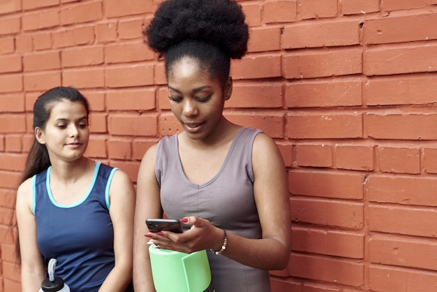Immagine di incredibili giovani donne atletiche davanti a un muro di mattoni, che guardano nel telefono. due amiche ridono del post sui social media.