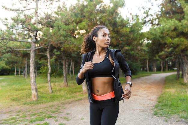 Immagine della ragazza americana 20s che indossa tuta nera e auricolari che si allena, mentre correva attraverso il parco verde