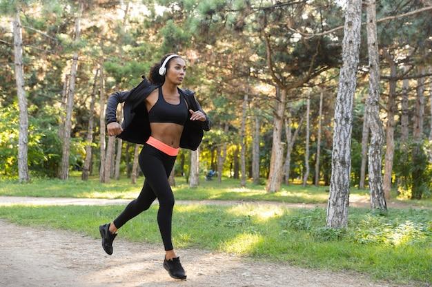 Immagine di una donna americana 20s che indossa tuta nera e cuffie che lavorano, mentre corre attraverso il parco verde