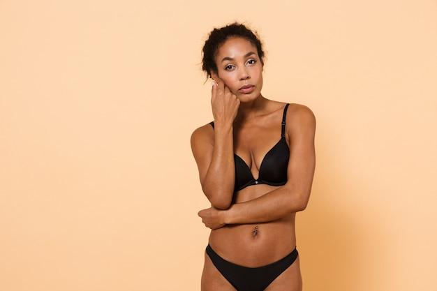 Immagine della donna americana che indossa lingerie nera, in piedi isolato sul muro beige