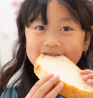 L'immagine di una ragazza asiatica con lunghi capelli neri che mangia pane naturale senza zucchero per la salute e una buona colazione per i bambini ogni giorno.