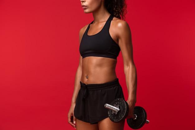 Immagine della donna afroamericana atletica in abiti sportivi neri che alza il manubrio, isolato sopra la parete rossa
