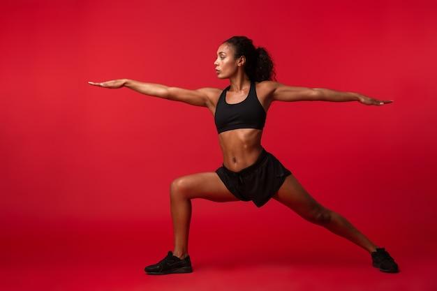 Immagine della donna afroamericana atletica in abiti sportivi neri che allunga il suo corpo, isolato sopra la parete rossa