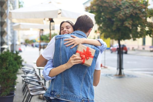 Immagine di una donna attraente con scatola regalo che abbraccia il suo uomo. Foto Premium